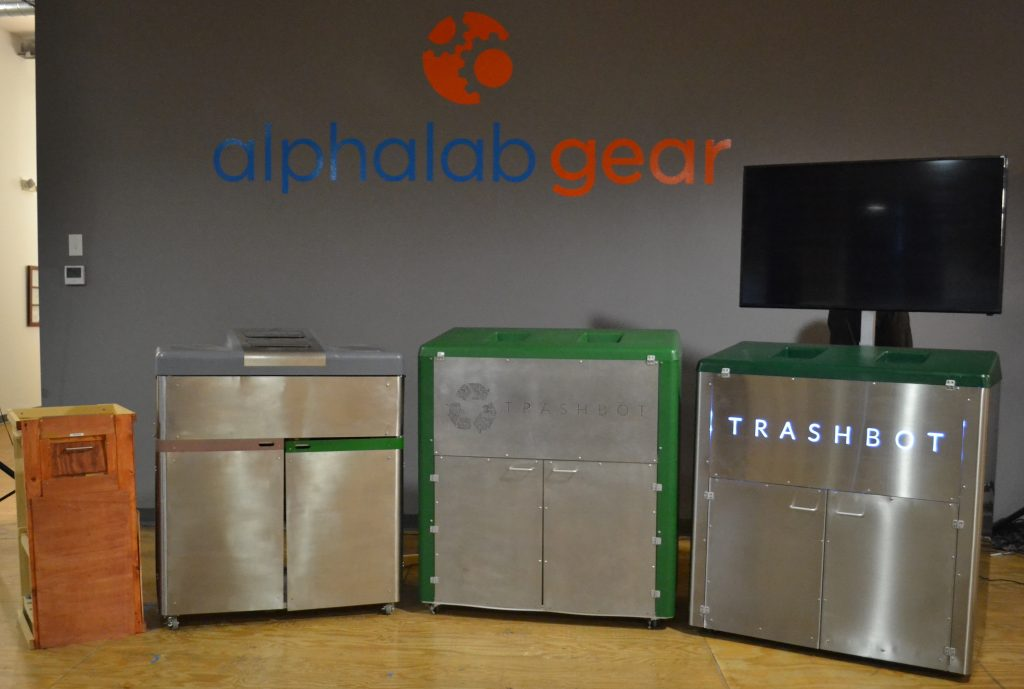 A picture of all the different designs of TrashBot. Starting with the original wooding prototype, then a prototype hacked out of an outdoor grill, then the front/back design with recycling logo, and finally the current version with side-by-side trash deposit holes.